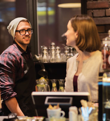 A male and female staff members behind the counter in a cafe