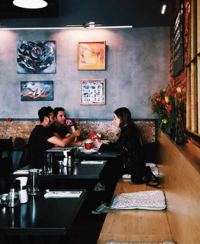 2 males and a female sitting at a table in the restaurant